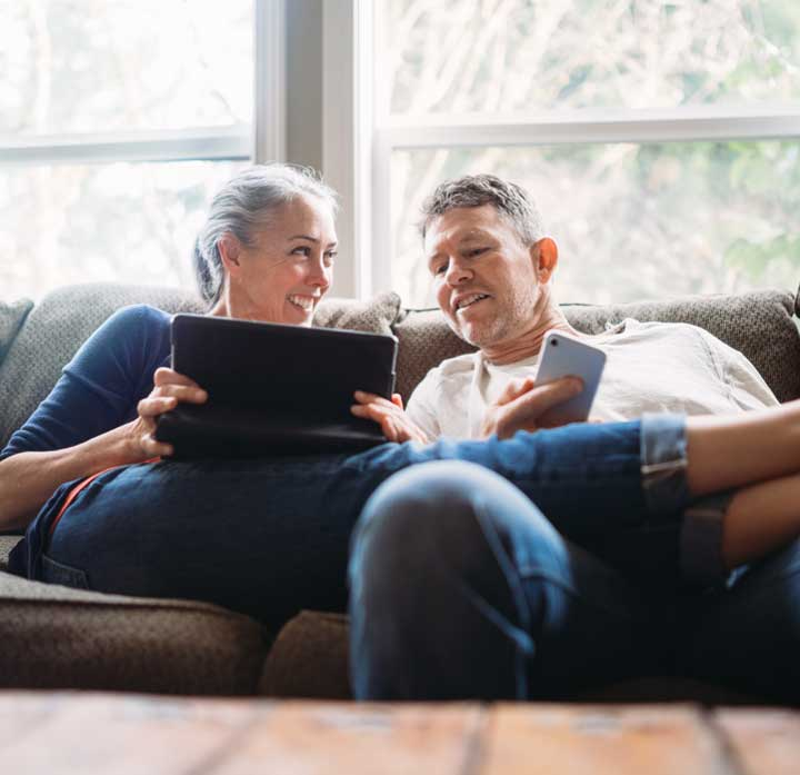 Woman Showing Man Tablet Display Sitting Comfortably Together On Couch